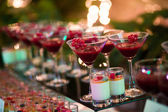 Beautiful line of different colored cocktails with smoke on a Christmas party, tequila, martini, vodka, and others on decorated catering bouquet table on open air party — Stock Photo