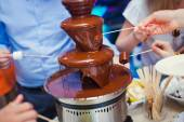 Vibrant Picture of Chocolate Fountain Fontain on childen kids birthday party with a kids playing around and marshmallows and fruits dip dipping into fountain — Stock Photo