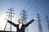 Businesswoman in front of power lines with arms oustretched — Stock Photo