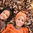 Kids lying on leaves — Stock Photo #80938388