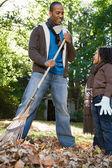 Padre e figlia rastrellare le foglie — Foto Stock
