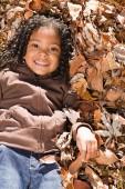 Ragazza sdraiata in foglie — Foto Stock