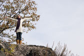 Exhilarated woman standing on rocks — Stock Photo
