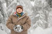 Ragazzo con una palla di neve nella foresta nevosa — Foto Stock