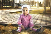 Cute little girl is sitting on the yellow autumn grass — Stock Photo