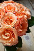 Beautiful wedding bouquet of apricot roses on wooden background — Stock Photo