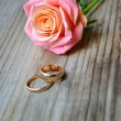 Two engagement golden rings with a beautiful wedding pink rose — Stock fotografie #52306105