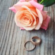 Two engagement golden rings with a beautiful wedding pink rose — Stock fotografie