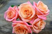Beautiful bouquet of pink and apricot roses on wooden background — Stock Photo