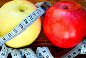 Diet concept with red and yellow apples and blue measuring tape on wooden table — Stock Photo