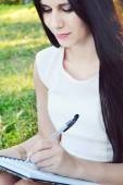 Young brunette woman with beautiful hands writing in her diary and smiling — Stock Photo