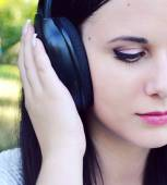 Beautiful brunette woman in big headphones listening to the music — Stock Photo