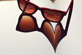 Red vintage sunglasses on a notebook giving the shadow on a heart — Stock Photo