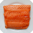 Big piece of salmon fillet on a white plate — Stock Photo #53556211
