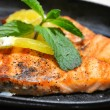 Two grilled salmon steaks with lemon and mint herb on black plate — Stock Photo #53650945