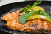 Two grilled salmon steaks with lemon and mint herb on black plate — Stok fotoğraf