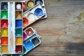 Colorful paints and brushes arranged as a frame on wooden table — Stock Photo