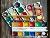 Colorful paints and brushes on wooden table — Stock Photo