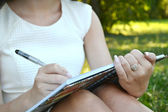 Woman with beautiful hands writing in her diary — Stock Photo
