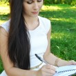 Young brunette woman with beautiful hands writing in her diary and smiling — Stock Photo #54497301