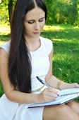 Jonge brunette vrouw met mooie handen schrijven in haar dagboek en glimlachen — Stockfoto