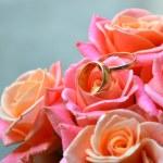dwa pierścionki zaręczynowe, złote na wesele piękny bukiet róż — Zdjęcie stockowe #59091255