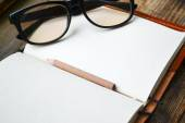 An empty retro notebook with old paper, little pencil, glasses and leather cover — Stock Photo
