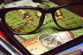 Reading glasses on geographical atlas — Stock Photo