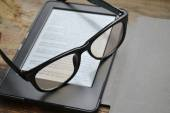 Black ereader with retro glasses on wooden table — Stock Photo