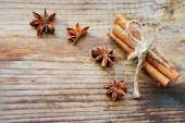 Cinnamon sticks and spicy anise stars on wooden table — Stock Photo