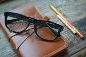 An old notebook in leather cover with pencils and glasses on wooden table — ストック写真
