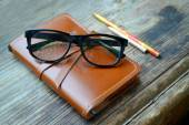 An old notebook in leather cover with pencils and glasses on wooden table — Stock Photo