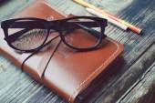 An old notebook in leather cover with pencils and glasses on wooden table — Foto de Stock