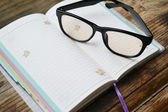 An empty retro daily planner with black pencil and reading glasses — Foto de Stock