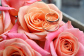 Two engagement golden rings on a beautiful wedding bouquet of pink roses — Stock Photo