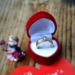 Red heart shaped ring box with platinum engagement ring, angels and a Valentine's card  on wooden table — Stock Photo #63431893