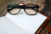 An empty retro notebook with old paper, reading glasses and leather cover — Stock Photo