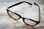 Siyah vintage okuma gözlüğü ahşap masa üstünde bilgisayar için — Stok fotoğraf
