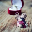Red heart shaped ring box with platinum engagement ring and a pair of lovers on wooden table — Stock Photo #63839495
