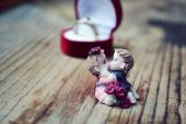 Red heart shaped ring box with platinum engagement ring and a pair of lovers on wooden table — Foto de Stock