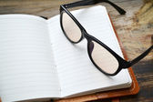 An empty retro notebook with old paper, glasses and leather cover — Stok fotoğraf