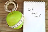 Diet concept with green apple, a notebook and a measuring tape on wooden table — Stock Photo