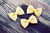 Uncooked butterfly shaped pasta farfalle on wooden table — Stock Photo