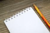 Ένα άδειο ρετρό σημειωματάριο και ένα μολύβι σε ξύλινο τραπέζι — Φωτογραφία Αρχείου