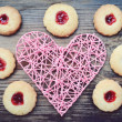 Romantic concept with handmade pink heart and lots of homemade cookies with jam on wooden table — Stock Photo #65390477