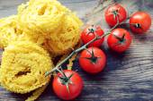 Bunch of small red cherry tomatoes with raw pasta Reginette (Mafaldine) on wooden table — Stock Photo