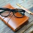 An old notebook in leather cover with pencils and glasses on wooden table — Stock Photo #65515007