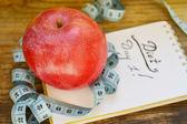 Concept de régime avec la pomme rouge, un carnet et un bleu, mètre à ruban sur table en bois — Photo