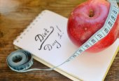 Diet concept with red apple, a notebook and blue measuring tape on wooden table — Stock Photo