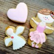 Gingerbread in a shape of heart and angel with pink and white icing and little cute ballet dancer on wooden table — Stock Photo #66002249